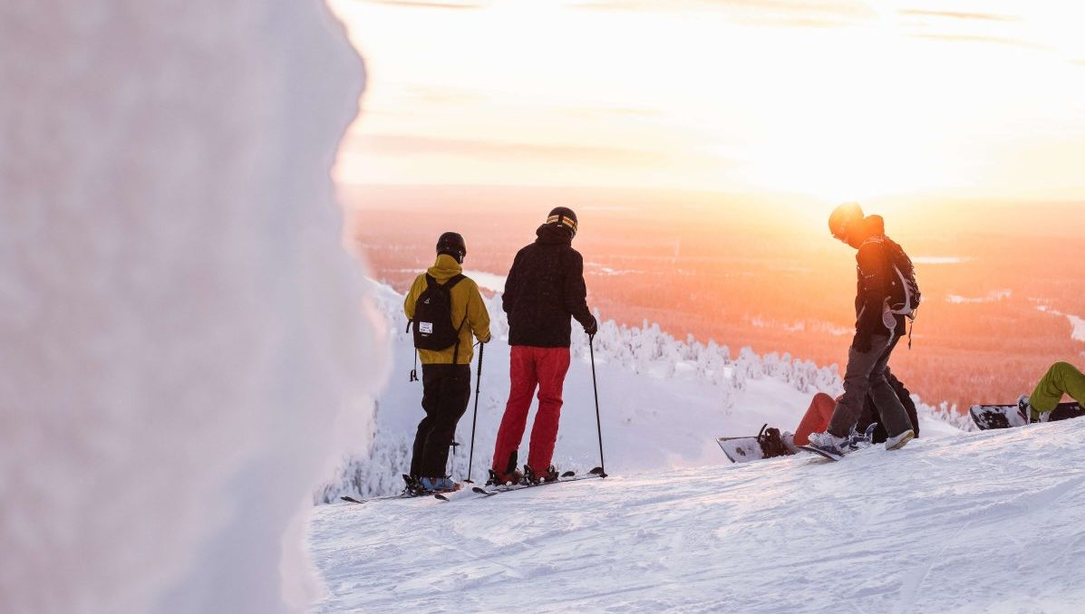 skiers in front of a sunset