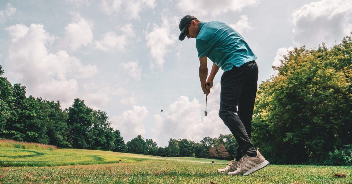golfer hitting ball on golf course